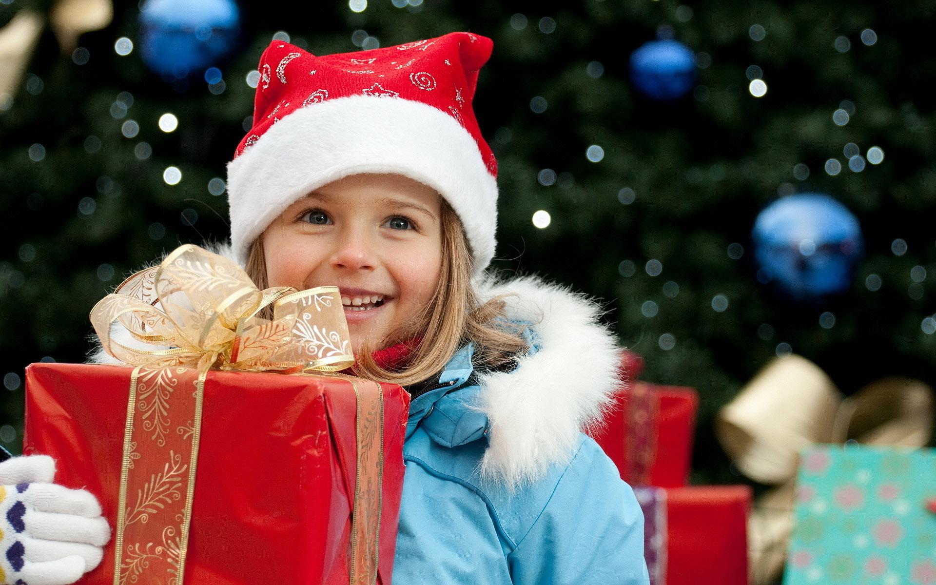HDoboi.Kiev.ua - Девочка с подарком на фоне елки, обои на телефон зима новый год