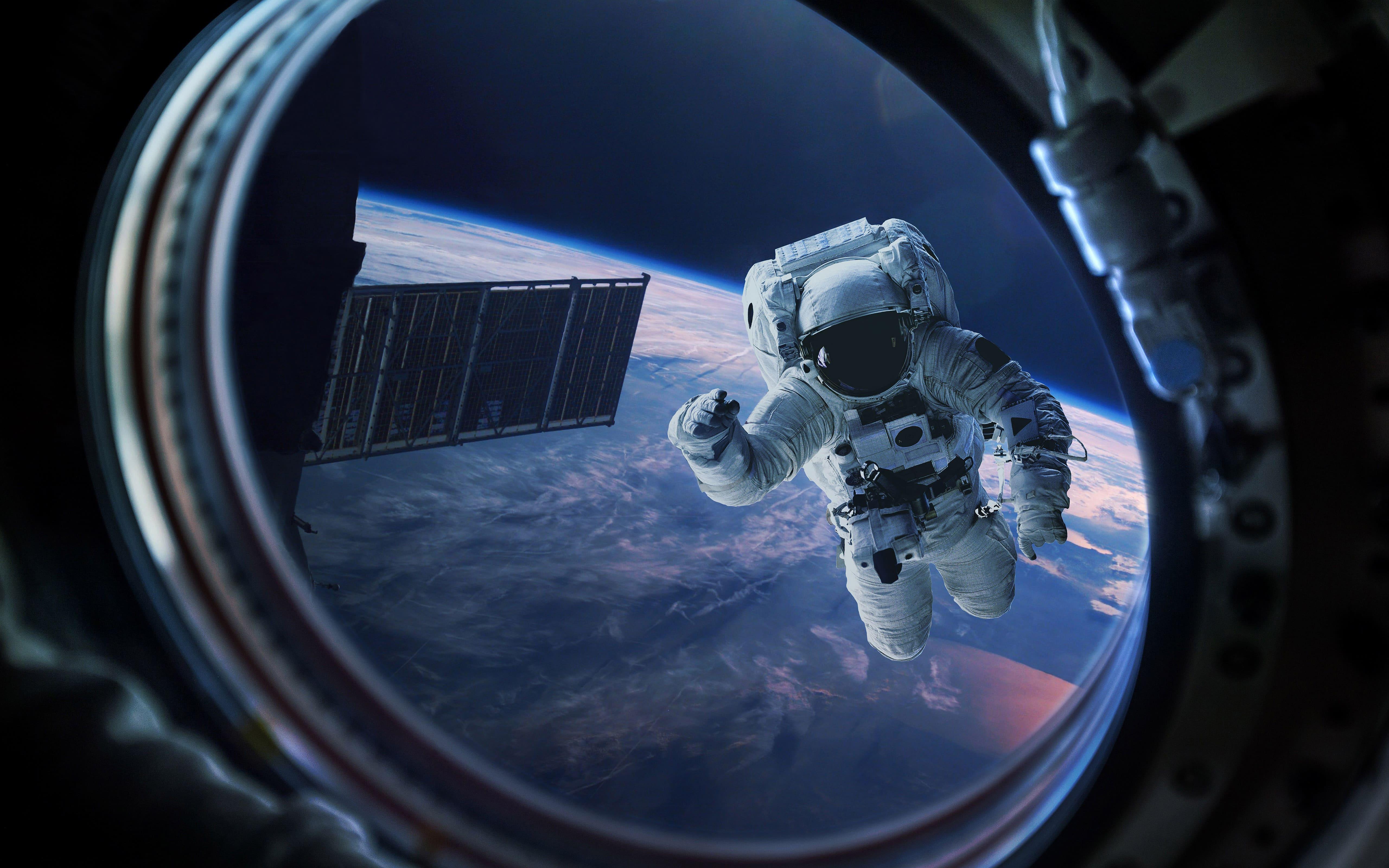 Астронавт в иллюминаторе из космоса, 5k ultra hd, 5120 на 3200 пикселей