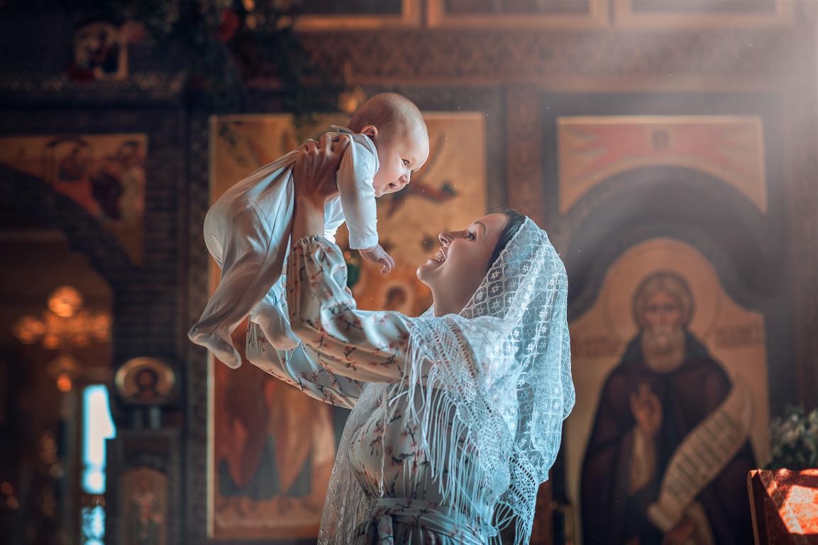 Счастливая женщина с ребенком на руках крестит младенца, 5120 на 3410 пикселей