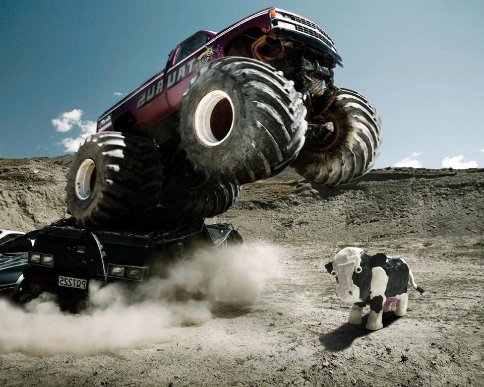 Джип с гигантскими колесами хочет раздавить корову, fullscreen, 1280 на 1024 пикселей